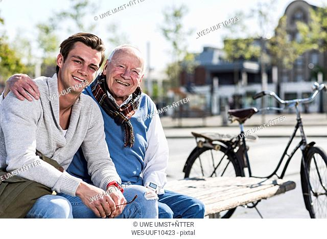 Portrait of happy senior man with adult grandson sitting on a bench