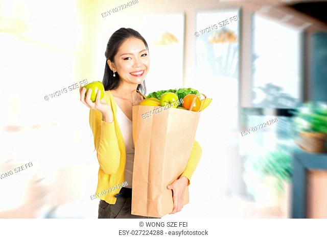 Young Asian female hand holding shopping paper bag filled with fruits and vegetables in market store or cafe