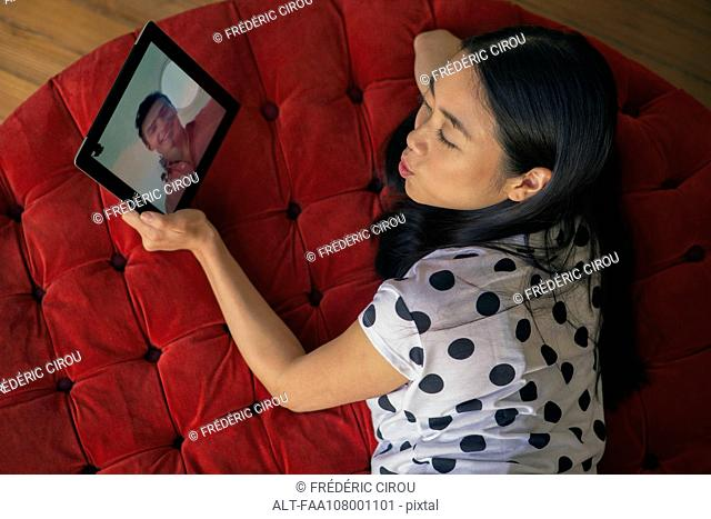 Woman blowing kiss at boyfriend while video conferencing on digital tablet