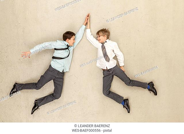 Business boys giving high five against beige background