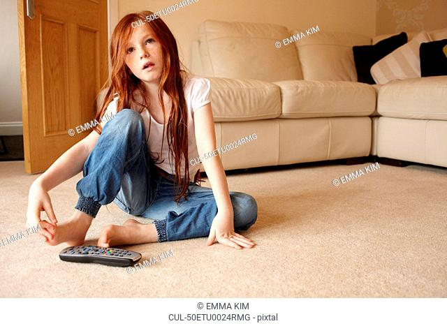 Girl watching television in living room