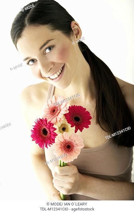 A young woman holding a bunch of flowers to camera