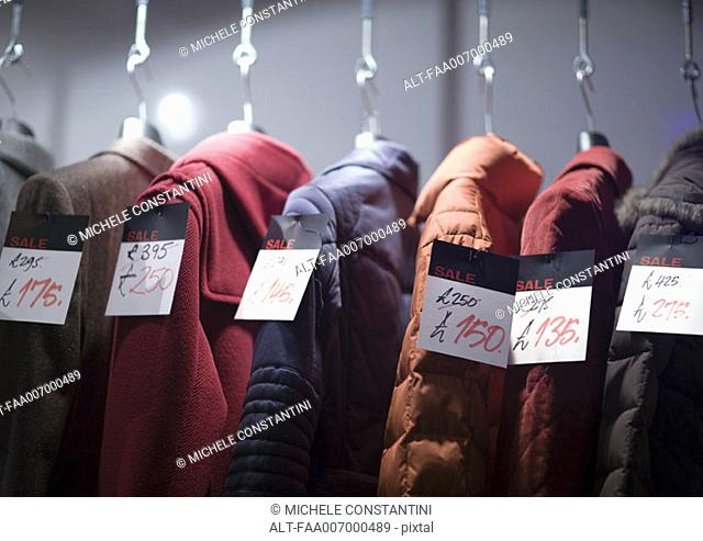 Coats on rack with tags showing sale prices