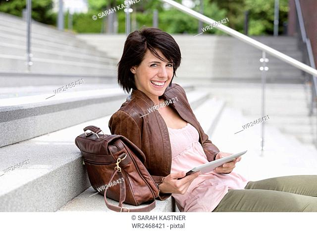 Woman sitting on stairs and using a Tablet PC
