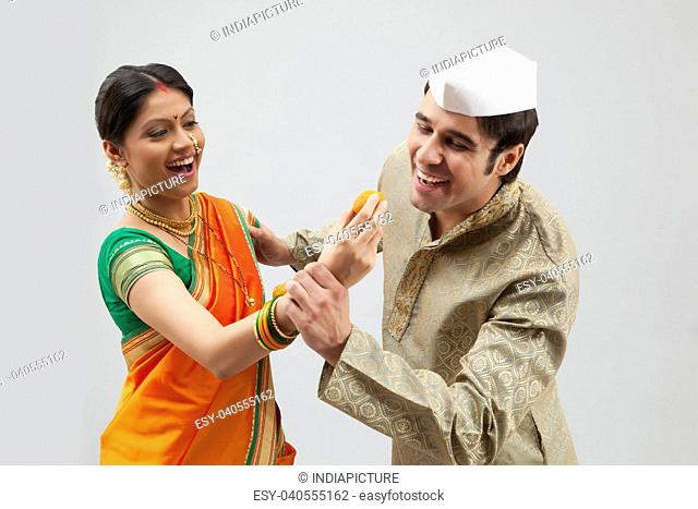 Maharashtrian man trying to eat a laddoo from a woman's hand