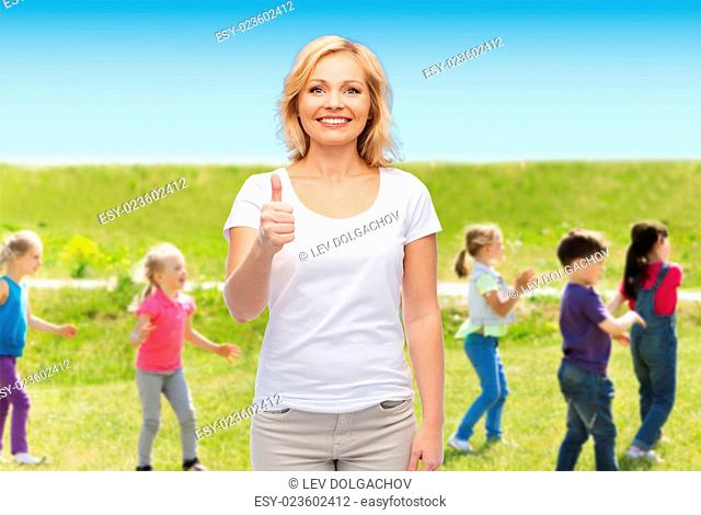 gesture, advertisement, children, parenthood and people concept - smiling woman in blank white t-shirt showing thumbs up over group of little kids outdoors...