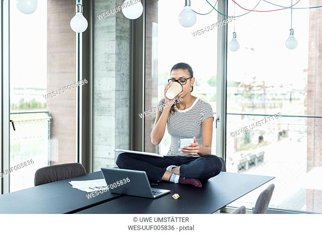 Young woman sitting on conference table looking at cell phone