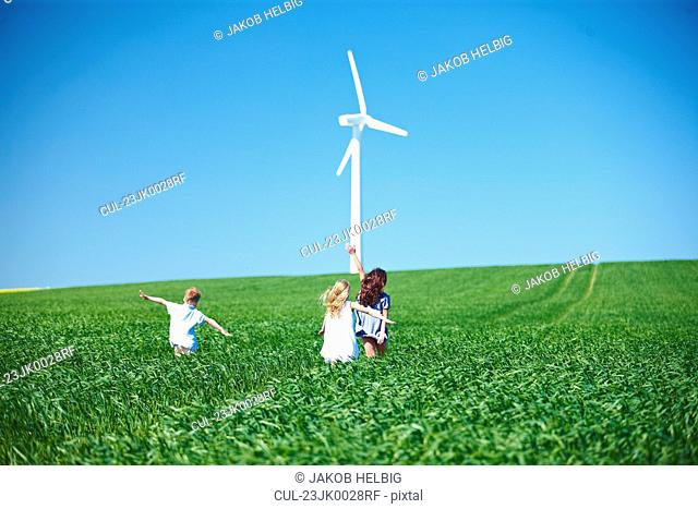 Wind turbine and childrens play in field