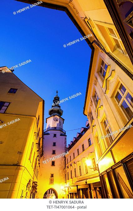 Illuminated townhouses and tower at dusk
