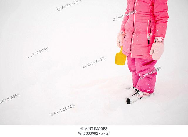 Girl wearing pink winter overall and mittens standing outdoors in the snow