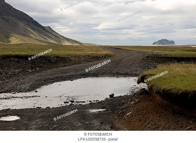 Landscape of mountain and pasture with rural dirt road and puddles
