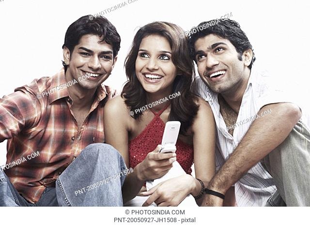 Close-up of a young woman and two young men smiling