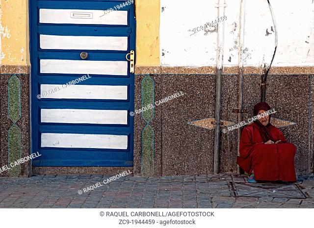 Elder woman sitting on the street in Essaouira medina, Morocco