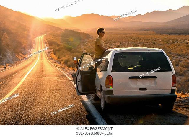 Man by car on open road, San Jose del Cabo, Baja California Sur, Mexico
