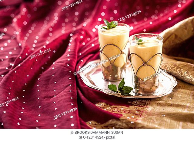 Mango lassi in two glasses on a tray (India)