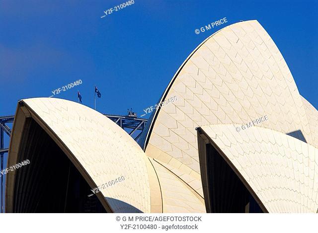 roof of Sydney Opera House framed against the peak of the Sydney Harbour Bridge
