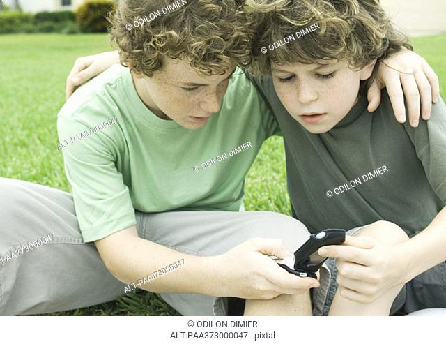 Two boys looking at cell phone