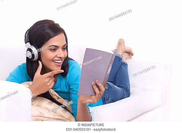 Young woman listening to music while reading