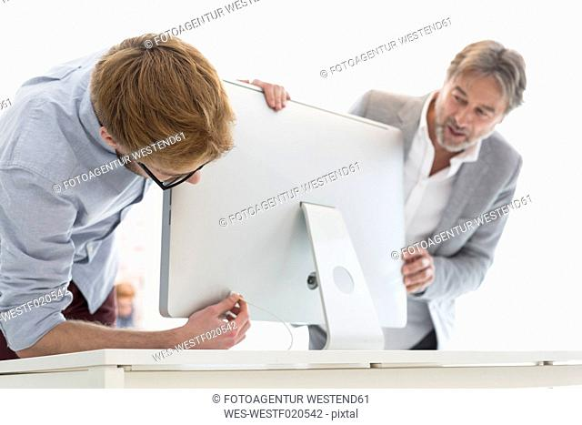 Two men in office connecting computer screen
