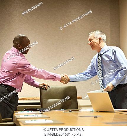 Businessmen shaking hands in meeting