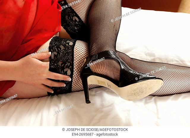 A partial view of a woman's legs in fish net stockings, high heel shoe and a hand