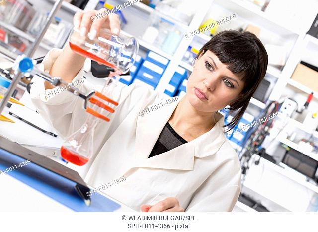 Female laboratory assistant pouring liquid in a laboratory