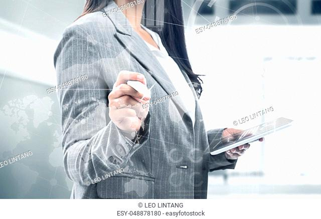 Business woman holding digital tablet and drawing with marker on virtual screen which display the interface of financial chart and world maps