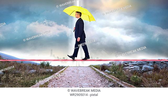 Businessman carrying umbrella while walking on rope