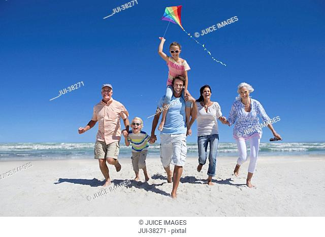 Happy multi-generation family with kite running on sunny beach