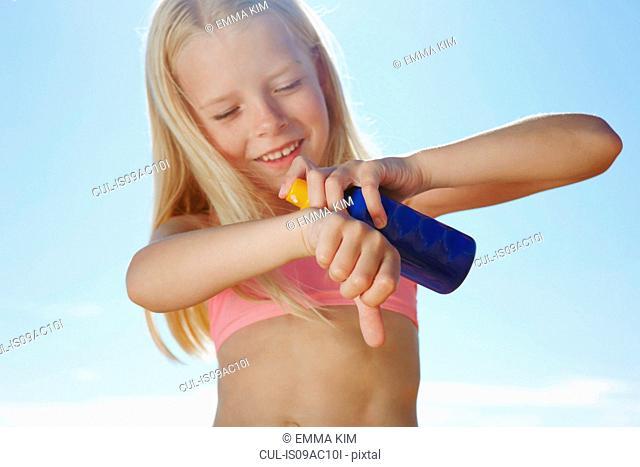 Girl spraying sunblock on hand