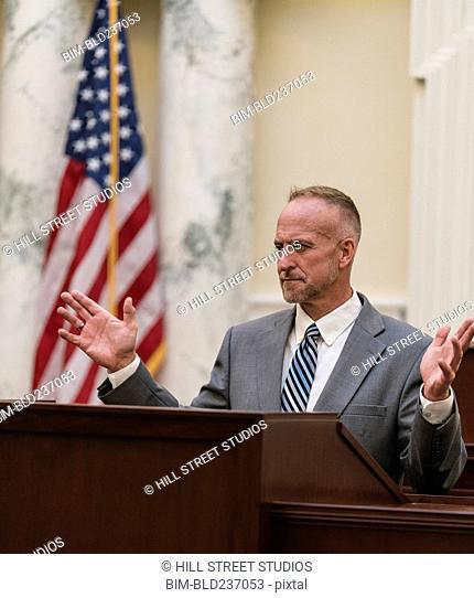 Caucasian politician gesturing at podium