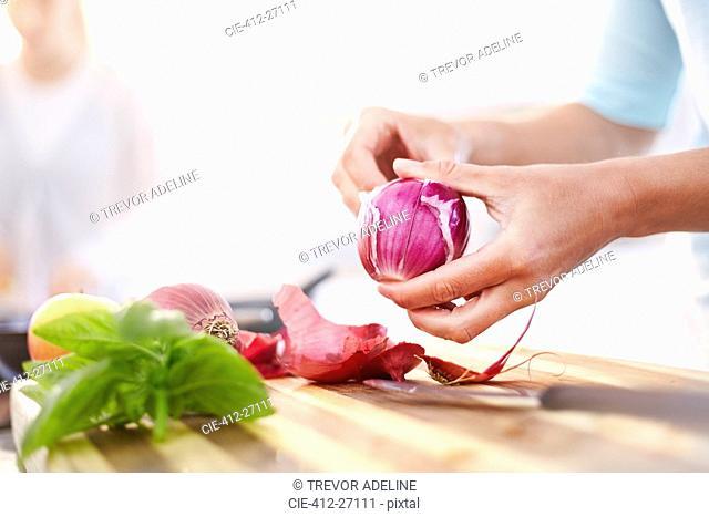 Woman peeling red onion in kitchen