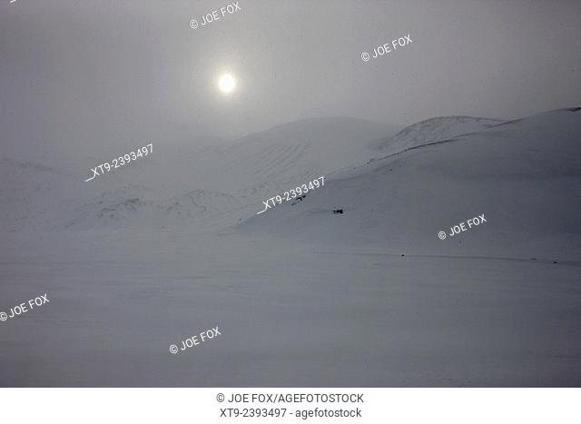 sun breaking through white out snowstorm whalers bay deception island Antarctica