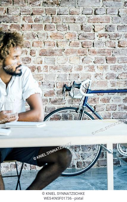 Young man at desk thinking with bicycle in background