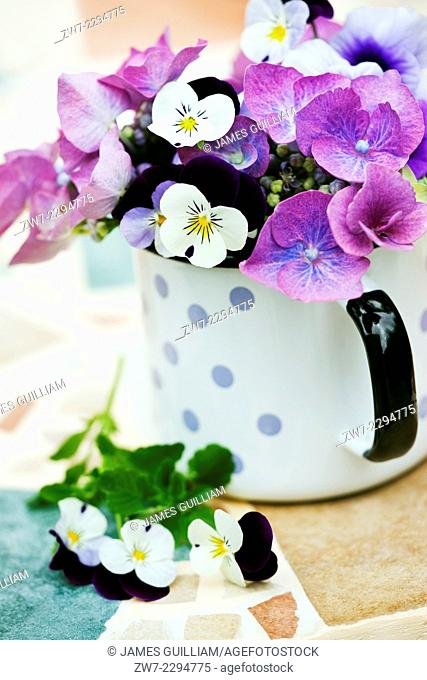 Cup containing Hydrangea and Viola flowers