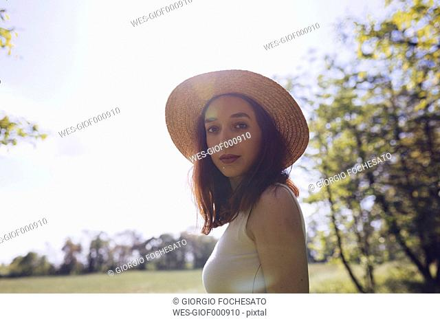 Portrait of young woman wearing straw hat in nature