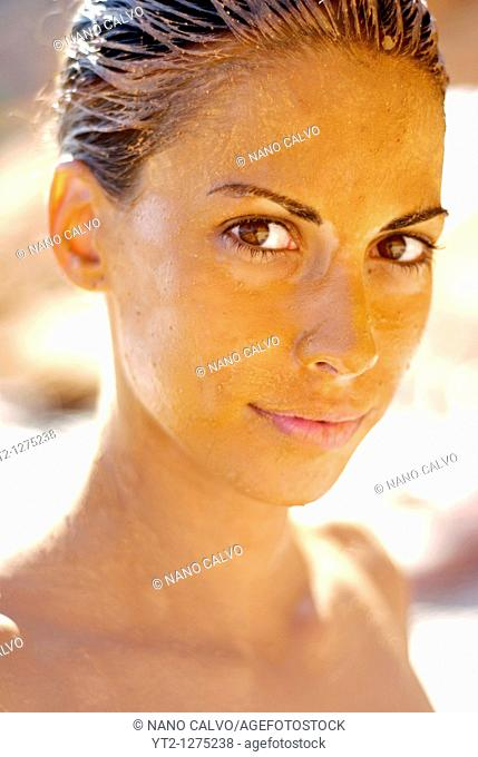 Young attractive woman covered in mud on the beach