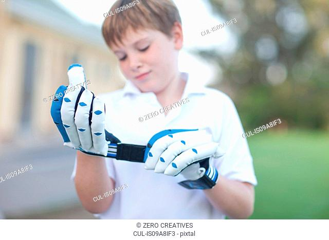 Boy putting on cricket gloves