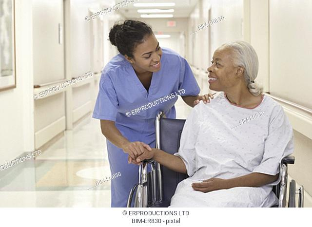 African female nurse reassuring senior patient in wheelchair