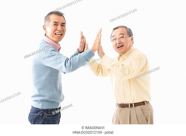 Two senior men high fiving