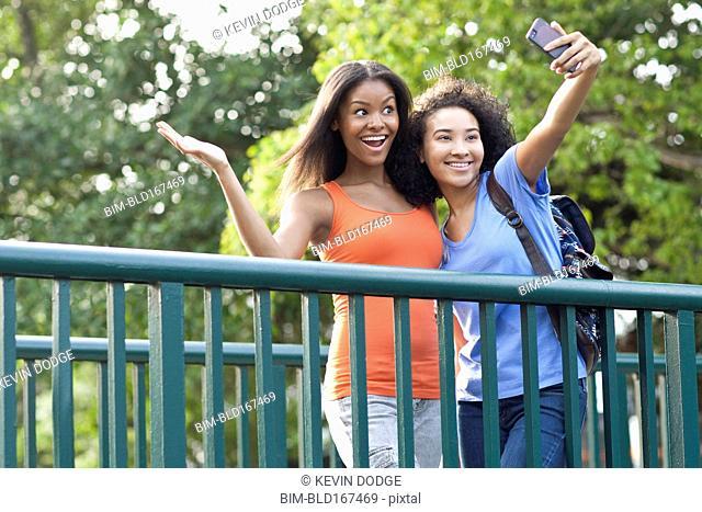 Black women taking selfie on walkway outdoors