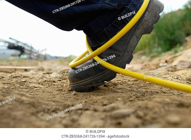 Detail of a leg of a construction worker tripping on a building site