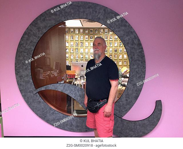 Q for Queer, a gay man stands in front of the round window in a Pride library full of gay literature, art, and other material, Ontario, Canada