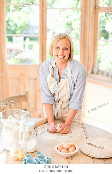 Smiling woman kneading dough on kitchen table