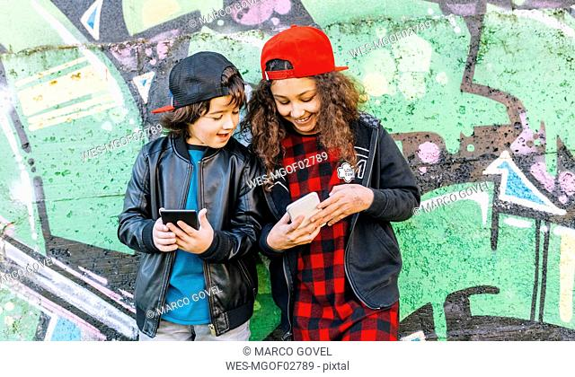 Two children standing in front of graffiti wall looking at cell phone