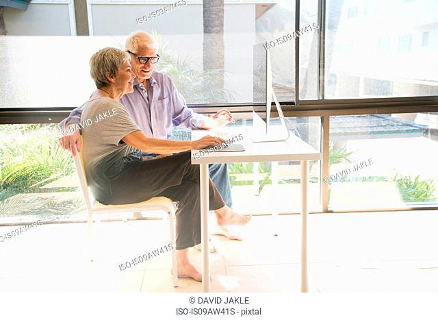 Senior couple using computer, looking at computer screen