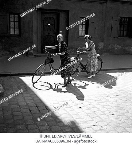Zwei Damen schieben ihre Fahrräder über das Kopfsteinpflaster von Augsburg, Deutschland 1930er Jahre. Two ladies pushing their bicycles through the old city of...