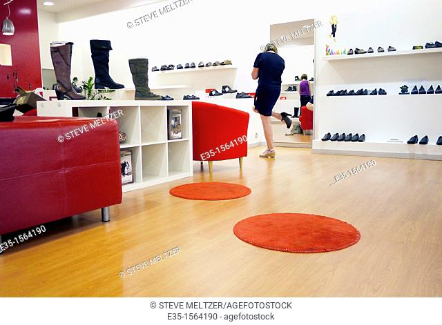 A woman tries on shoe's at a modern shoe store