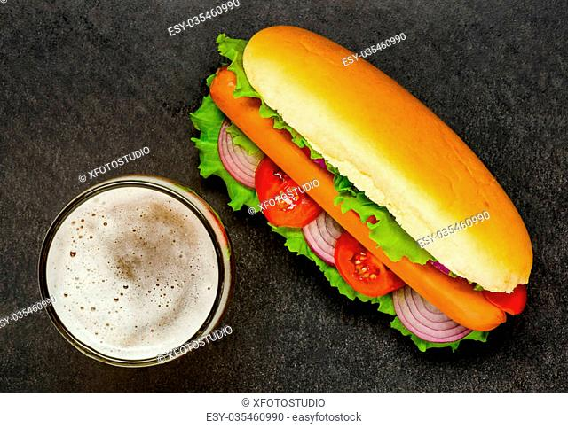 Hot Dog Sandwich with sausage, tomato, onions and sliced Bun on a Dark Background with glass of Beer