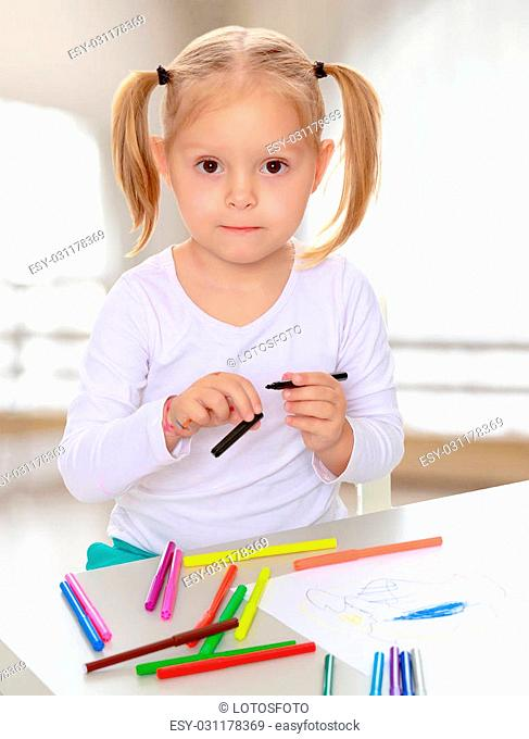 The concept of pre-school education of the child among their peers . in gaming room with a large arched window.Pretty little blonde girl drawing with markers at...
